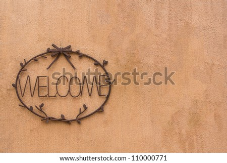 steel cast welcome sign on earth tone rough textured cement wall - stock photo