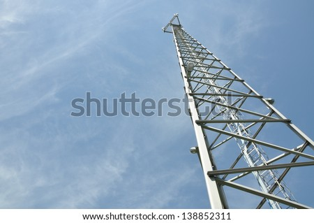 Steel cell phone tower against a blue sky - stock photo