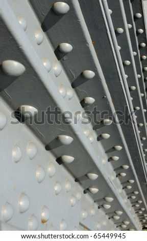 Steel construction fastened with rivets - industrial background. Shallow depth of field - stock photo