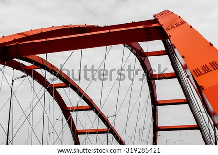 Steel construction of the red bridge on a monochromatic background  - stock photo