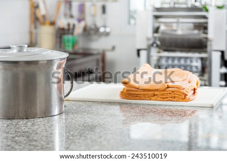 Steel container with ravioli pasta sheets on countertop in commercial kitchen - stock photo