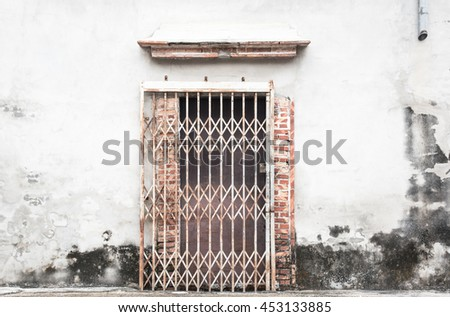 Steel door stretch on the damaged concrete wall, cracked brick wall texture - stock photo