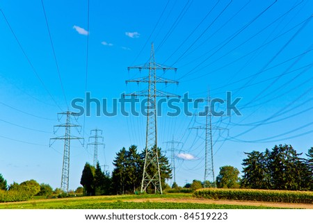Steel electricity pylon on bright blue sky - stock photo