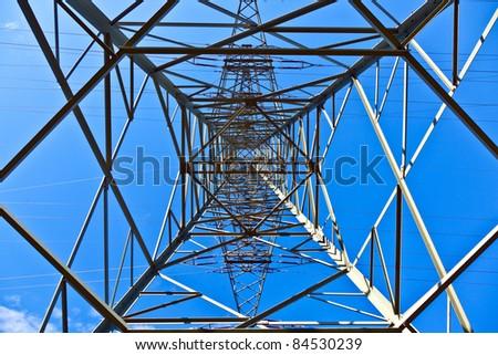 Steel electricity pylon on bright blue sky - stock photo