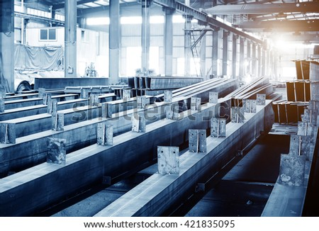 Steel factory floor, stacked with a lot of steel - stock photo