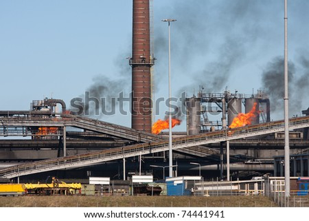 Steel factory with smokestacks and gas flaring - stock photo