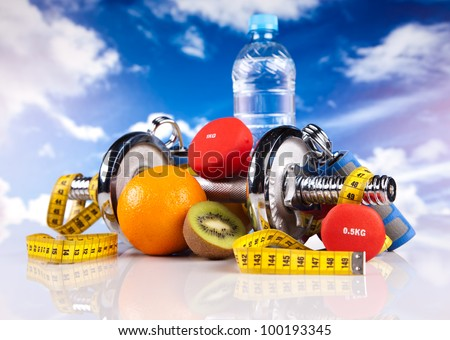 steel fitness dumbbells, bottle of water, fruits and colorful strings - stock photo