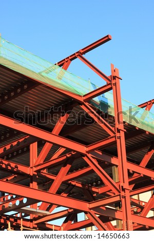 Steel framework of a new high rise building during building in later afternoon light. - stock photo