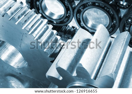 steel gears and ball-bearings in a blue toning concept - stock photo