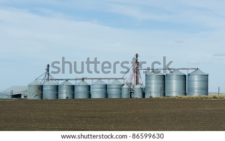 Steel grain storage silos and freshly harvested field - stock photo