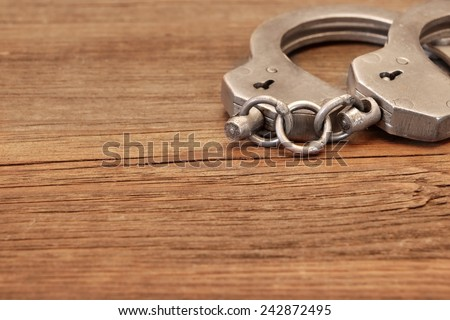 Steel Handcuffs on Wooden Table. Background with space for text or image. - stock photo