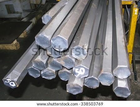 steel hexagon bars in factory warehouse - stock photo