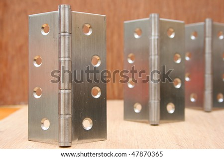 Steel hinge with others behind it.