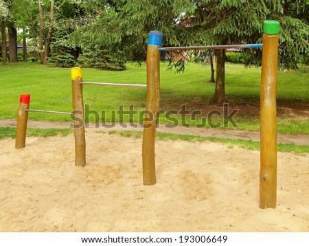 Steel horizontal bars on wooden pillars in children playground. Orange sand below bars, green park in the background. - stock photo