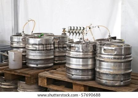 Steel industrial barrels of beer stocked in storage - stock photo