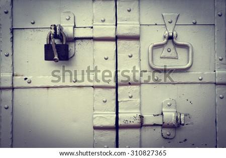 Steel lock on the rusty grey metal door - stock photo
