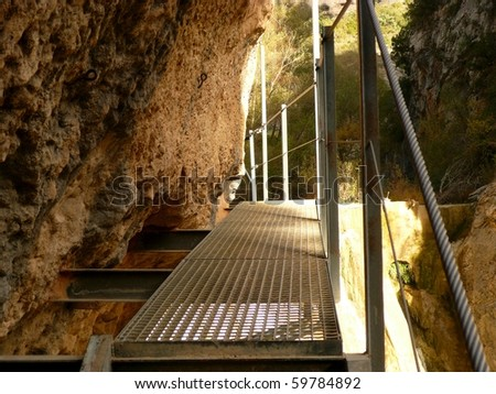 steel-metal walk way running along a rock face adjacent to running water near a village called alquezar in huesca, spain