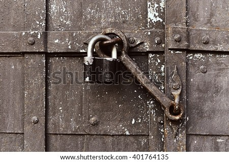 Steel padlock keeping the old door heck at the iron forged old door. Focus at the padlock and door heck. Textured metal rusty background - stock photo