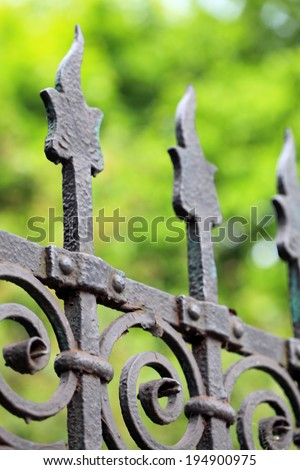steel picket fence on green background - stock photo