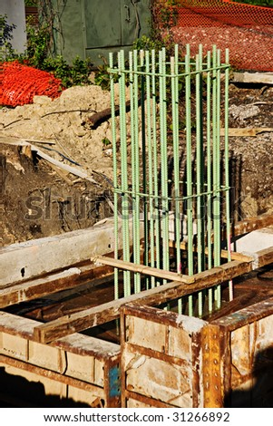 Steel rebar sunk into a large framed block of freshly poured concrete that is part of the support system for a new bridge that is being built. - stock photo