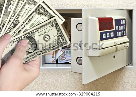 Steel safe with money and female hands holding dollars