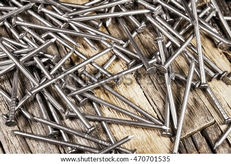 Steel shiny nails on wooden background. Stock image macro.