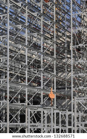 Steel structure of a high rack warehouse and a crane during construction - stock photo