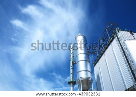 Steel tank/silo with reflective sun light and industrial smokestack with blue cloud sky background. - stock photo