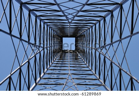 Steel tower with blue sky square far above. Industrial pattern