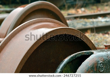 Steel train wheels sitting exposed to the elements in an old rail yard - stock photo