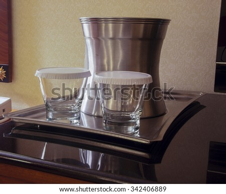 Steel tray with two tumblers covered by paper lids and bucket for ice