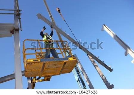Steel worker on cherry picker. - stock photo