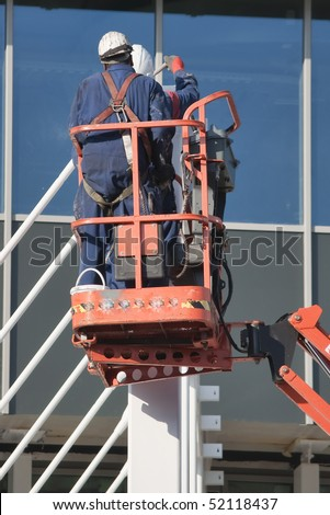 Steel workers wearing safety harness on a cherry picker - stock photo