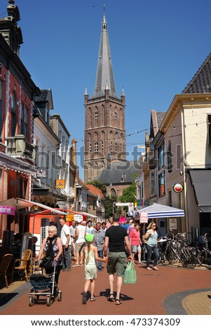 STEENWIJK, THE NETHERLANDS - JULY 20: Tourists visiting the city center of Steenwijk. In the background the St. Clemens tower. Photo taken at July 20th, 2016 in Steenwijk, The Netherlands.