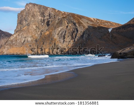 Steep cliffs rise above Kvalvika beach, Lofoten Island, Norway - stock photo