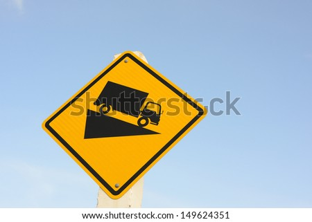 Steep grade hill ahead warning road sign on the blue sky back ground - stock photo
