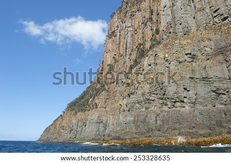 Steep high rocky cliff coast at Bruny Island, Tasmania, Australia, popular tourist destination, with view over Southern Ocean to horizon, summer blue sky as copy space. - stock photo
