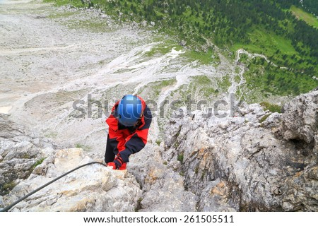 "Steep passage on via ferrata ""Meisules"" with woman climber holding the steel cable, Sella massif, Dolomite Alps, Italy - stock photo"