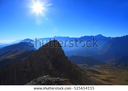 steep peak on a background of the blue mountains and bright sun. Rocky ridge, Caucasus.