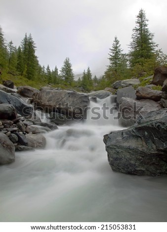 Steep rapid stream of foamy Alpine river. White waves of brook flowing down over boulders and stones,  high water level after heavy rains. - stock photo