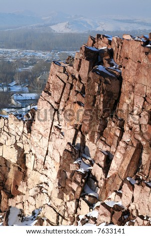 Steep rock in the winter. Village - stock photo