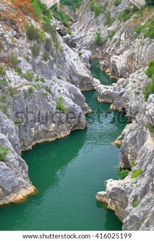 Steep rocky gorges above green river in Saint Guilhem le Desert, Languedoc Roussillon, France - stock photo