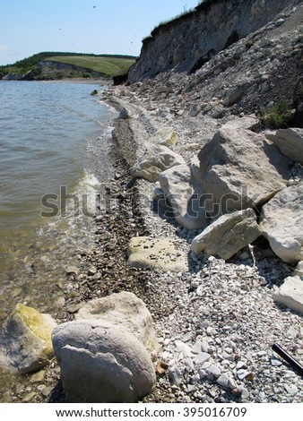 Steep rocky river bank against a blue sky - stock photo