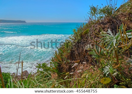 Steep slope on an ocean coast in the summer. Northern Spain, Cantabria, ocean. Summer, the coast the blue ocean and the flat line of the horizon in the distance has grown with a grass a - stock photo