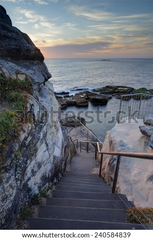 Steep stairs lead down the cliff face to Giles Baths rockpool on the northern end of Coogee, Sydney Australia.  - stock photo