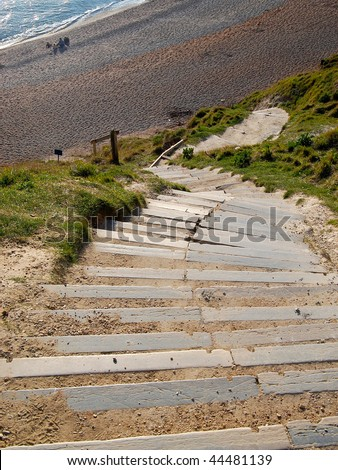 Steep stone steps down the cliff to a pebbled beach - unidentifiable people on the beach give a sense of scale. Durdle Door, Dorset (UK) - stock photo