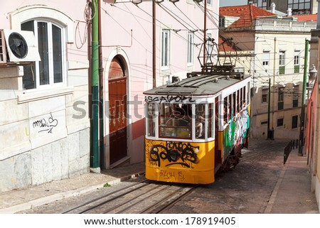Steep street Calcada da Gloria with traditional trams in Lisbon, Portugal - stock photo