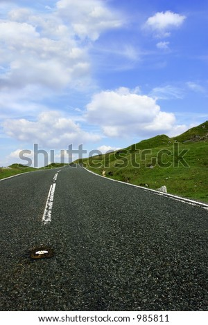 Steep uphill remote mountain road, with grass banks on either side and a blue sky with puffy white clouds. Set in the Brecon Beacon National Park, Wales, United Kingdom. Taken from a low perspective. - stock photo