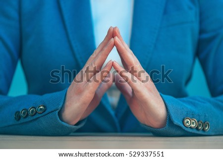Steepled fingers of business woman as hand gesture sign of confidence, self-esteem, power and domination.