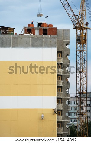 steeplejacks on a concrete wall of a under construction house - stock photo